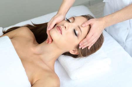 mooie vrouwen: Mooie jonge vrouw tijdens gezichtsmassage in cosmetische salon close up Stockfoto