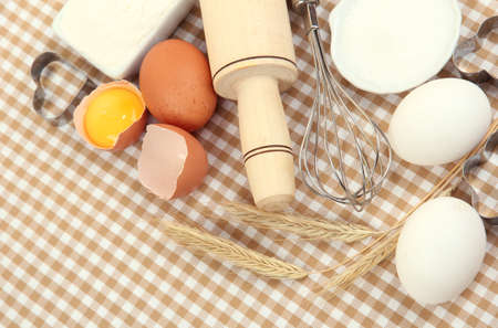 baking ingredients: Cooking concept. Basic baking ingredients and kitchen tools on tablecloth background Stock Photo