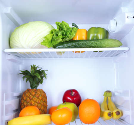 Milk bottles, vegetables and fruits in open refrigerator. Weight loss diet concept. photo