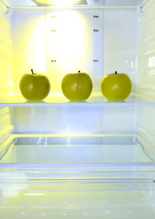 Apples in open empty refrigerator. Weight loss diet concept. photo