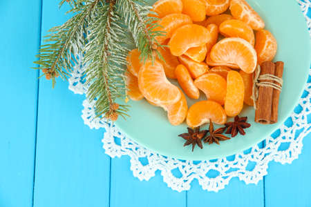 Tasty mandarines slices on color plate on blue background photo
