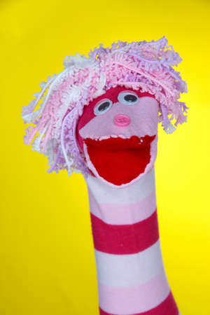 Cute sock puppet on yellow background photo