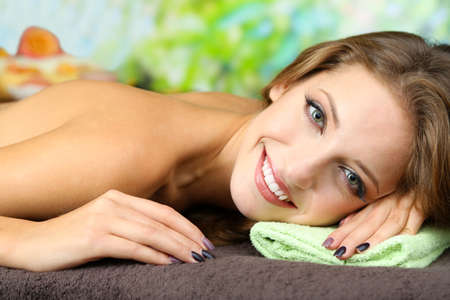Beautiful young woman on massage table on natural background Stock Photo - 24174923