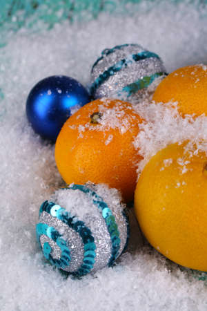 Christmas tangerines and Christmas toys on wooden table on snow photo