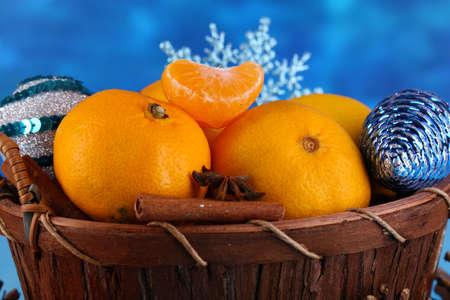 Christmas tangerines in basket on blue background photo