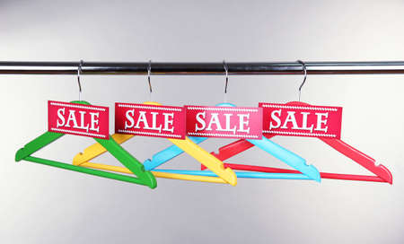 Wooden clothes hangers as sale symbol on gray background photo