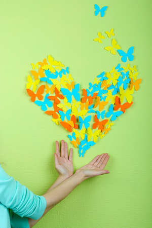 Paper butterflies on hands on green wall background Stock Photo