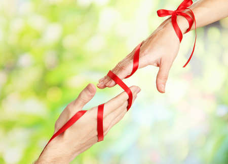 mans: Mans and girls hands tied with ribbon on bright background