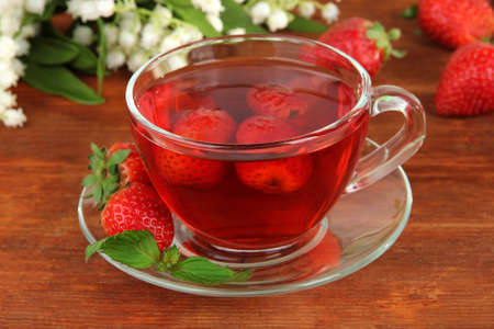 Delicious strawberry tea on table close-up photo