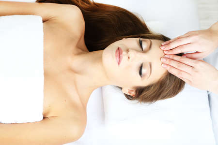 Beautiful young woman during facial massage in cosmetic salon close up Stock Photo - 24175038