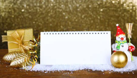 Empty calendar, New Year decor and fir tree on shiny golden background photo