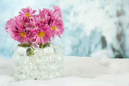 Beautiful flowers in vase with hydrogel on table on bright background