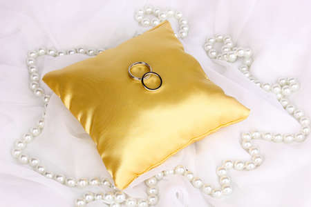 Wedding rings on satin pillow on white cloth background