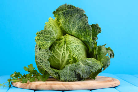 Fresh savoy cabbage on wooden table on blue background photo
