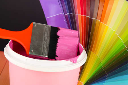 refurbishing: Paint pot, paintbrush and coloured swatches close up