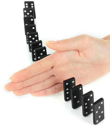Hand stopping dominoes falling isolated on white photo