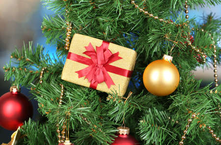 Gift on Christmas tree on room background photo
