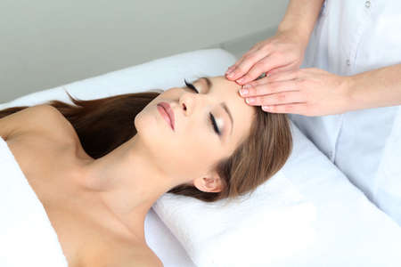 Beautiful young woman during facial massage in cosmetic salon close up Stock Photo - 24175303