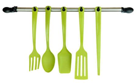 kitchen utensils: Utensilios de cocina de pl�stico sobre los ganchos de plata aislados en blanco Foto de archivo