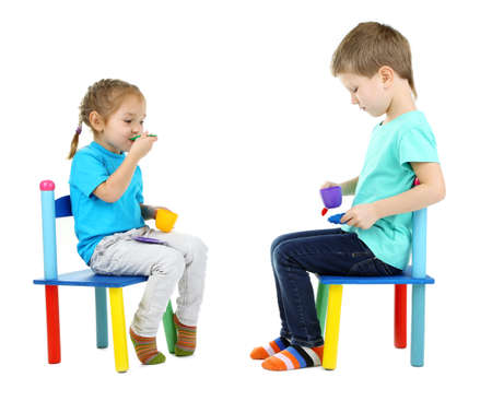 baby chair: Little children playing with colorful tableware isolated on white