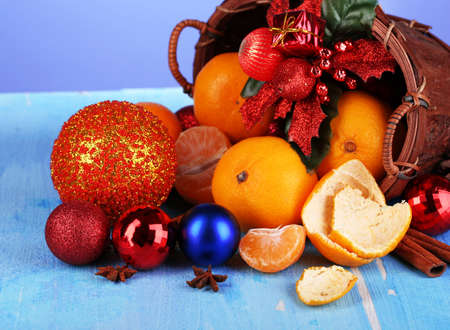Christmas tangerines and Christmas toys in basket on wooden table on blue background photo