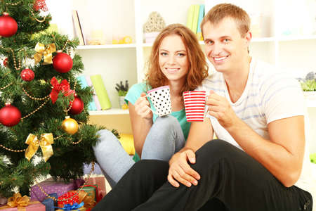 Happy young couple near Christmas tree at home photo