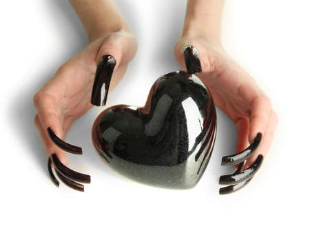Hands with scary manicure holding black heart , isolated on white photo