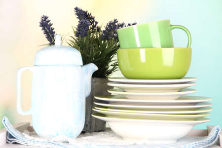 Beautiful white shelves with tableware and decor, on bright background, close-up photo