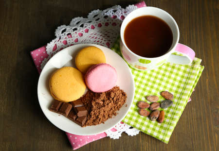 Cocoa in cup with sweets and cocoa powder on plate on wooden table photo