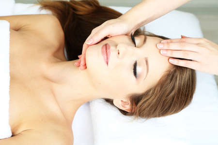 facial spa: Beautiful young woman during facial massage in cosmetic salon close up Stock Photo
