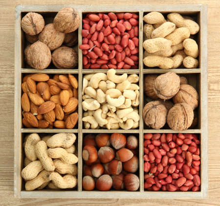 wooden box: assortment of tasty nuts in  wooden box on table