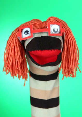 Cute sock puppet on green background photo