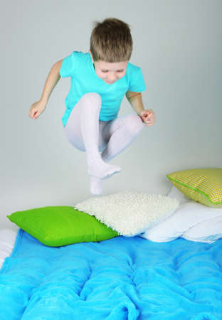 Little boy jumping on bed  photo