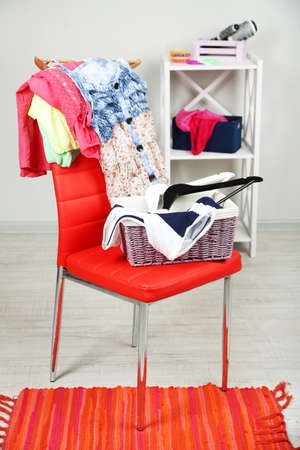 slut: Heap of  clothes on color chair,  on gray background Stock Photo