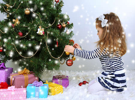 Little girl decorating Christmas tree with baubles in room photo