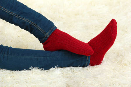 Female legs in colorful socks on  white carpet background