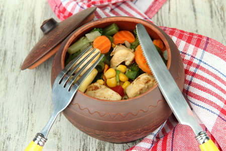Baked mixed vegetable with chicken breast in pot, on wooden background photo