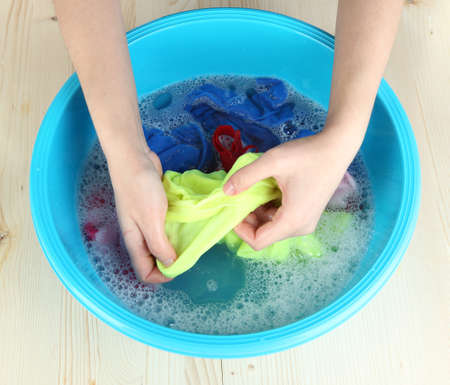 Hand washing in plastic bowl on wooden table close-up Stock Photo - 24032762