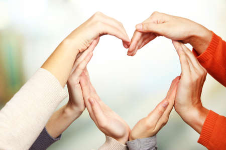 trust people: Human hands in heart shape on bright background