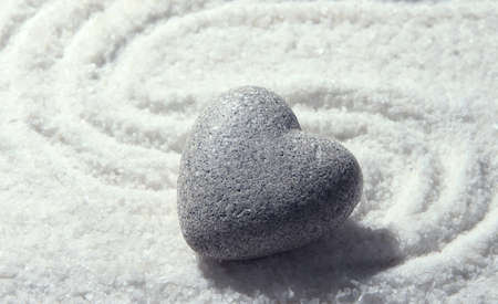 cold blooded: Grey zen stone in shape of heart, on sand background