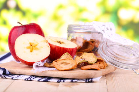 Dried apples in glass jar, on   bright background photo