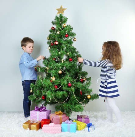 Kids decorating Christmas tree with baubles in room photo