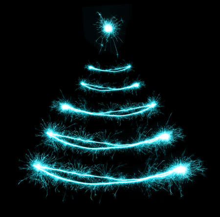 christmas eve: Christmas tree-shaped sparklers on black background
