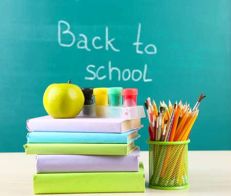 School supplies on table on blackboard background  photo
