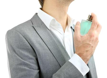 beau jeune homme: Beau jeune homme utilisant parfum isol� sur fond blanc