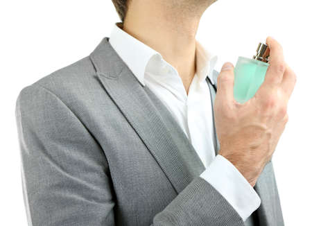 perfume spray: Handsome young man using perfume isolated on white