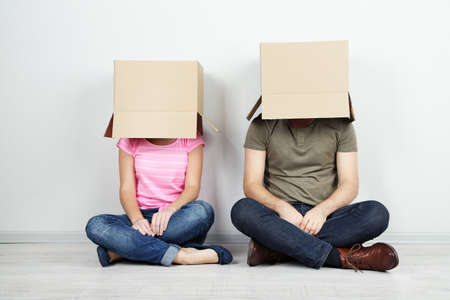 Couple with cardboard boxes on their heads sitting on floor near wall photo
