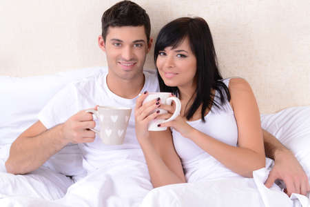 Couple in love drinking coffee in bed photo