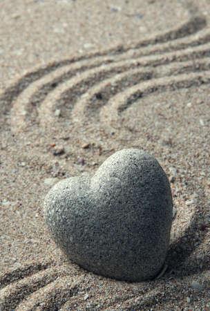 Grijze zen steen in vorm van hart, op zand achtergrond Stockfoto