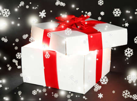 Gift box with bright light on it on dark grey background photo